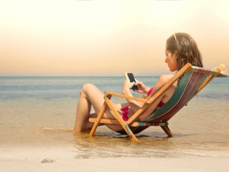 Young woman using her smartphone at the beach